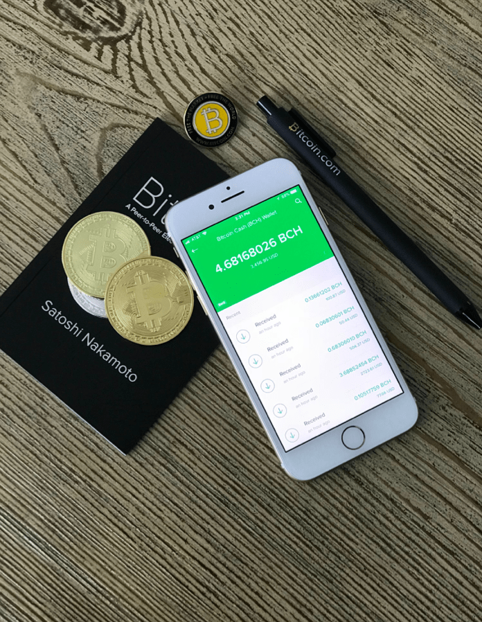 Bitcoin, phone and coins on the table